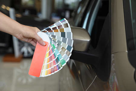 Young woman holding palette with color samples near modern car, closeup