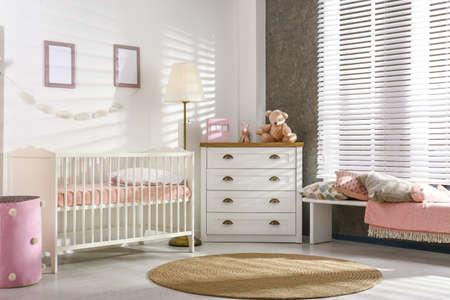 Cozy baby room interior with comfortable crib Standard-Bild