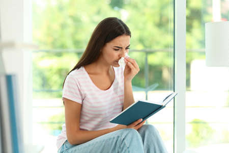 Young woman with book suffering from allergy at home