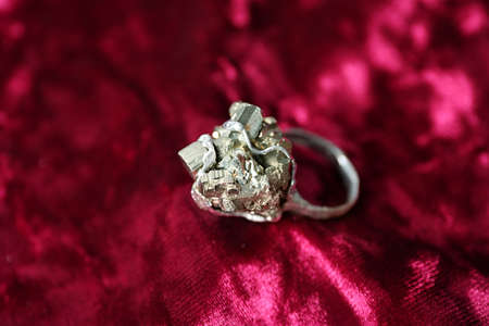 Beautiful silver ring with pyrite gemstones on burgundy fabric, closeup Stock Photo