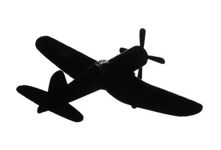 Dark silhouette of vintage toy military airplane on white background