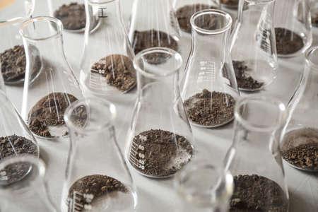 Cristalería con muestras de suelo en mesa gris. Investigación de laboratorio