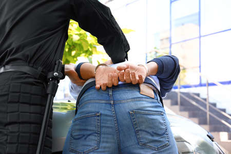 Police officer arresting criminal near car outdoors