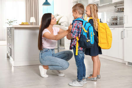 Happy mother and little children with school bags in kitchen