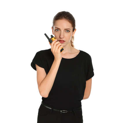 Female security guard in uniform using portable radio transmitter on white background