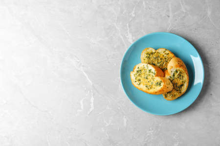 Slices of toasted bread with garlic, cheese and herbs on grey table, top view. Space for text
