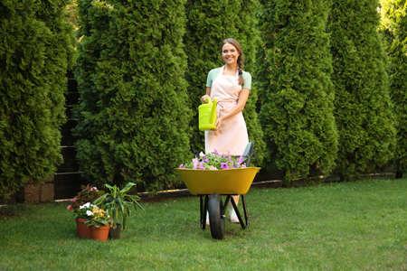 Happy young woman watering plants in garden