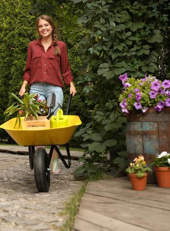 Female gardener with wheelbarrow and plants outdoors Reklamní fotografie