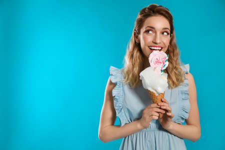 Portrait of young woman holding cotton candy dessert on blue background, space for text