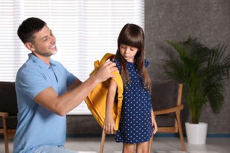 Glücklicher Vater, der seinem kleinen Kind hilft, die Schultasche zu Hause anzuziehen