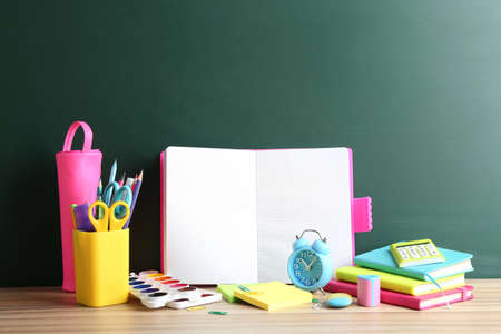 Different school stationery and blank notebook on table near chalkboard. Space for text Standard-Bild