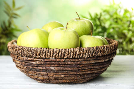 Wicker bowl of fresh ripe green apples on white wooden table against blurred background