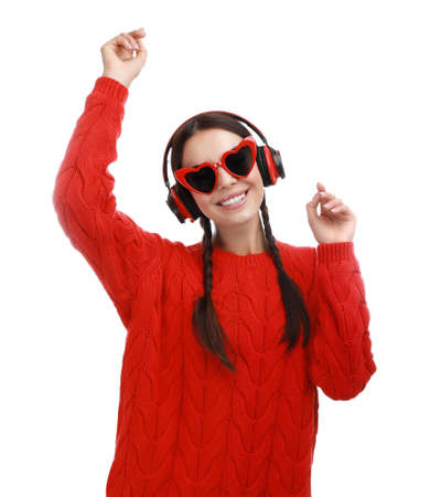 Young woman wearing heart shaped glasses listening to music on white background