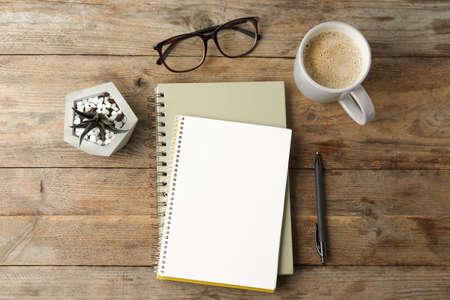 Flache Laienzusammensetzung mit Büromaterial und Tasse Kaffee auf Holztisch. Raum für Gestaltung Standard-Bild