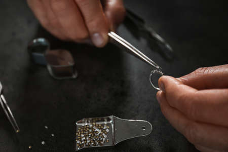 Male jeweler examining diamond ring in workshop, closeup view