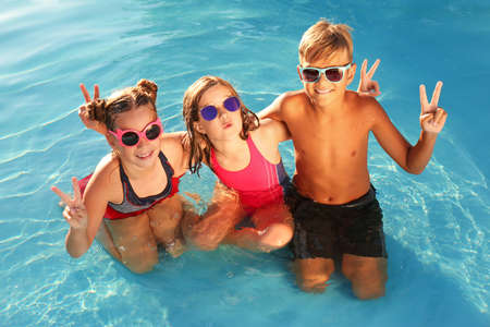 Happy children with sunglasses in swimming pool