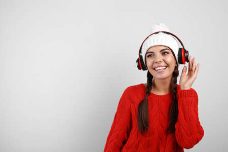 Young woman listening to music with headphones on grey background, space for text