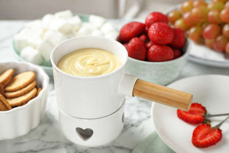 Fondue pot with white chocolate and different products on marble table