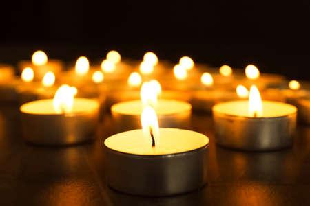 Brandende kaarsen op tafel in duisternis, close-up. Begrafenis symbool