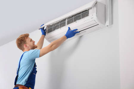 Professional technician maintaining modern air conditioner indoors