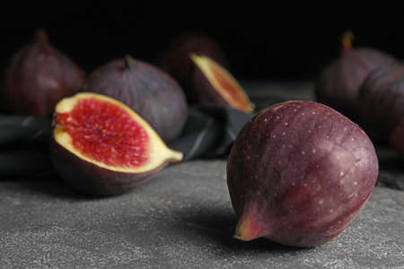 Tasty ripe fig fruits on grey table against dark background