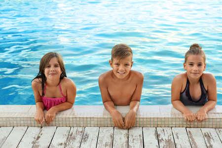 Niños felices en la piscina en un día soleado Foto de archivo
