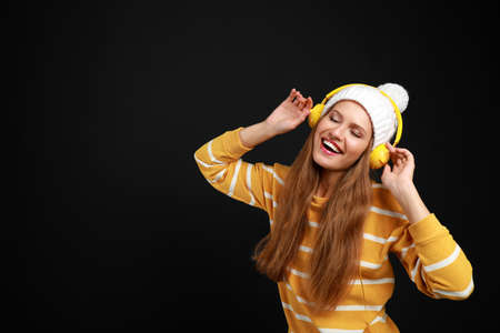 Young woman listening to music with headphones on black background, space for text