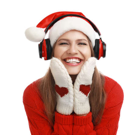 Young woman in Santa hat listening to Christmas music on white background