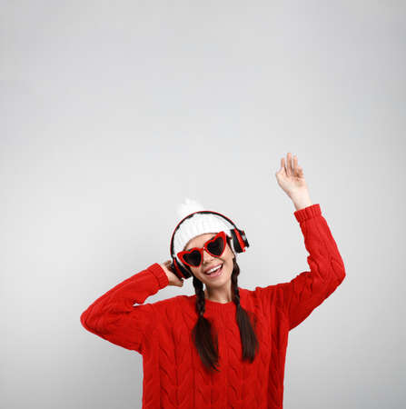 Young woman listening to music with headphones on grey background