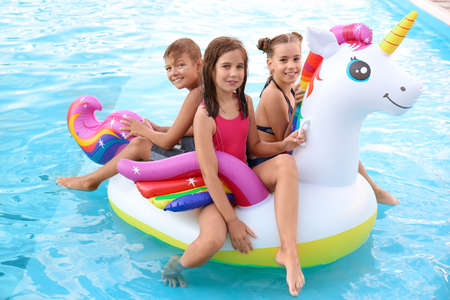 Happy children on inflatable unicorn in swimming pool