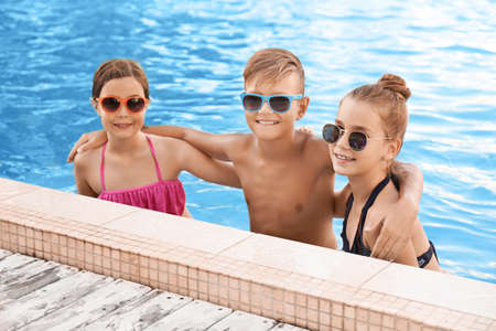 Happy children in swimming pool on sunny day Stock Photo