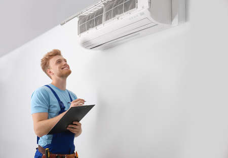Professional technician with clipboard near modern air conditioner indoors Imagens