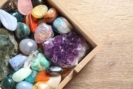 Box with different beautiful gemstones on wooden table, flat lay Stockfoto