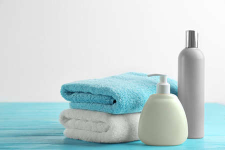 Folded soft towels and toiletries on light blue wooden table Reklamní fotografie