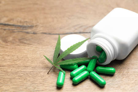 Hemp leaf and bottle with capsules on wooden table. Space for text Reklamní fotografie - 131133955