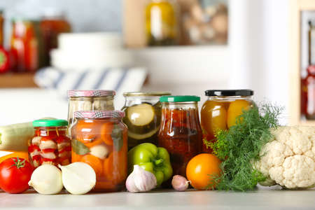 Fresh vegetables and jars of pickled products on wooden table