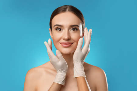 Doctor examining woman's face before plastic surgery on light blue background Stock Photo