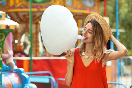 Happy young woman eating cotton candy in amusement park Stock Photo