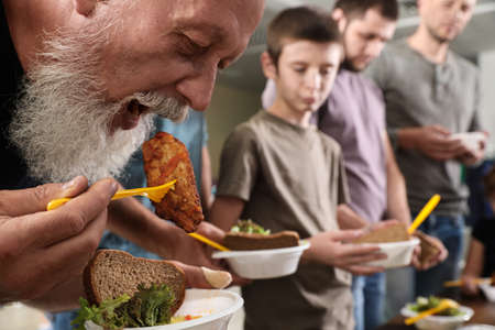 Senior man with other poor people eating food in charity centre