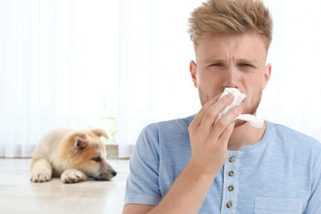 Young man suffering from allergy to dogs at home