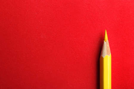 Yellow pencil on red background. Space for text 版權商用圖片