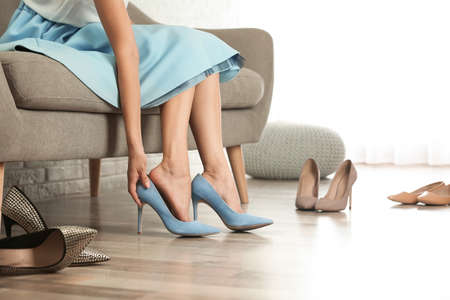Woman trying on different shoes indoors, closeup Stock Photo