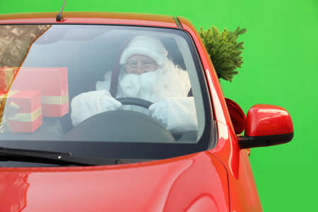Authentic Santa Claus with fir tree and presents driving car against green background