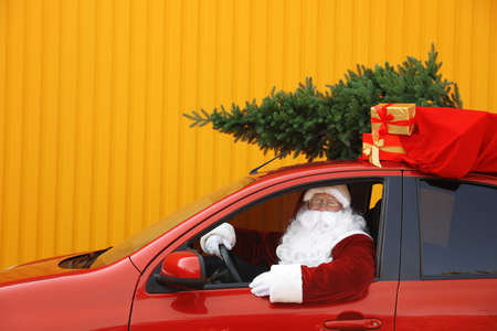 Authentic Santa Claus with fir tree and bag full of presents on roof driving car against yellow background