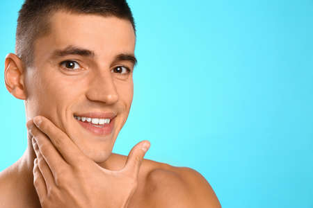 Handsome young man after shaving on light blue background, space for text