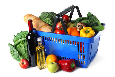 Shopping basket and grocery products on white background