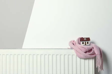 House model wrapped in pink scarf on radiator indoors, space for text. Winter heating efficiency