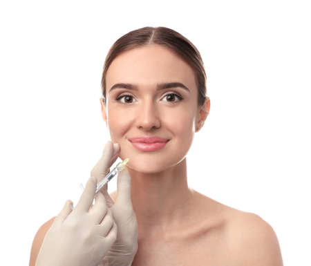 Beautiful woman getting facial injection on white background. Cosmetic surgery Foto de archivo