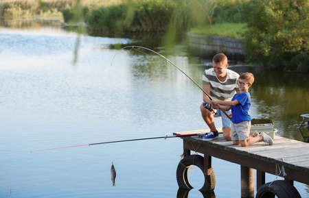 Dad and son fishing together on sunny day