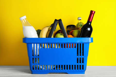 Shopping basket with grocery products on white wooden table against yellow background